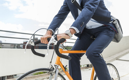 Businessman riding bicycle - UUF005337