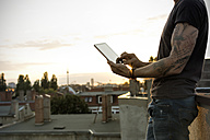 Germany, Berlin, Mature man on roof terrace using digital tablet - ONF000840