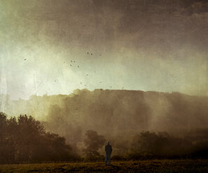 Man standing on meadow at sunset, digitally manipulated - DWI000552