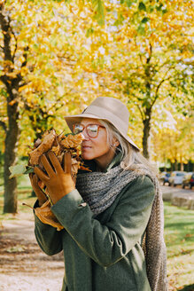 Portrait of woman smelling autumn leaves in her hands - CHAF001116