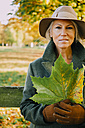 Portrait of woman wearing hat holding autumn leaf in a park - CHAF001125