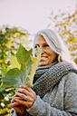 Smiling woman with grey hair wearing grey scarf holding autumn leaf - CHAF001137