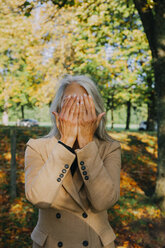 Woman in autumnal park hiding her face behind hands - CHAF001143
