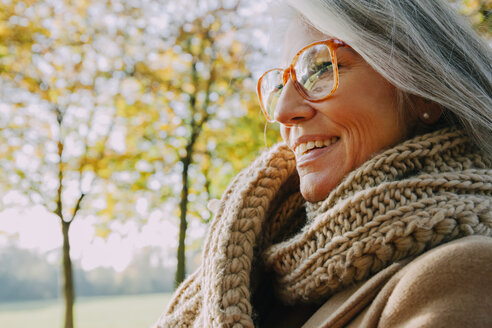 Portrait of smiling woman wearing scarf and glasses - CHAF001146