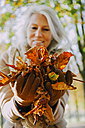 Woman holding autumn leaves in her hands - CHAF001149