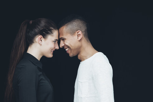 Happy young couple face to face in front of black background - CHAF001202