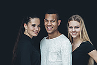 Group picture of two young woman and young man in front of black background - CHAF001207