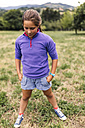 Girl standing on a meadow with hands in her pockets - MGOF000416