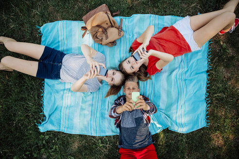 Three teenage friends with smartphones lying on blanket - AIF000066