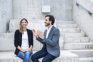 Two business people sitting on concrete steps - FMKF001750