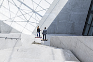 Two business people standing on skateboards in modern architecture - FMKF001736