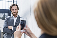 Businesswoman photographing her colleague with smartphone - FMKF001739