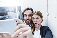 Portrait of two business people making faces while taking a selfie with smartphone - FMKF001742