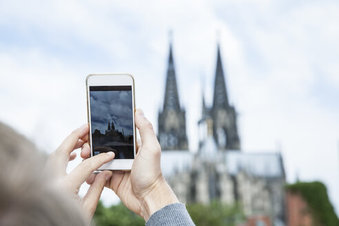 Germany, Cologne, young woman taking a picture of Cologne Cathedral with smartphone - FMKF001836
