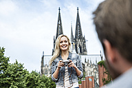 Germany, Cologne, portrait of smiling woman with camera looking at her boyfriend - FMKF001765