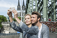 Germany, Cologne, young couple taking a selfie with smartphone at Hohenzollern Bridge - FMKF001768