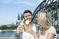 Germany, Cologne, happy young couple toasting with Koelsch glasses in front of Rhine River - FMKF001771