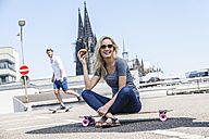 Germany, Cologne, portrait of young woman with bagel sitting on skateboard - FMKF001779