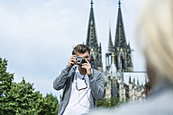 Germany, Cologne, man taking a picture of his girlfriend - FMKF001790