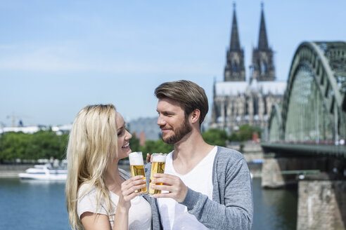 Germany, Cologne, happy young couple toasting with Koelsch glasses in front of Rhine River - FMKF001799