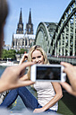 Germany, Cologne, young man taking a picture of his girlfriend with smartphone - FMKF001801