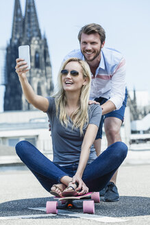 Germany, Cologne, portrait of smiling young couple taking a selfie with smartphone - FMKF001816