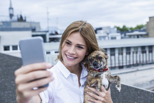 Portrait of smiling young woman taking a selfie with her dog on roof terrace - FMKF001821