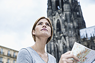 Germany, Cologne, portrait of young woman with city map in front of Cologne Cathedral - FMKF001805