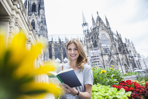 Germany, Cologne, portrait of young woman with book in front of Cologne Cathedral - FMKF001840