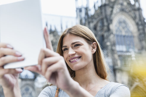 Germany, Cologne, portrait of smiling young woman taking a selfie in front of Cologne Cathedral - FMKF001810
