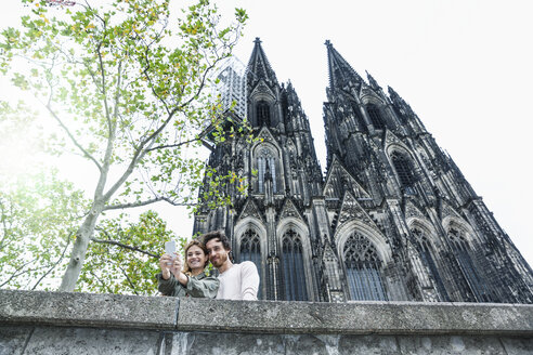 Germany, Cologne, portrait of young couple taking a selfie in front of Cologne Cathedral - FMKF001825