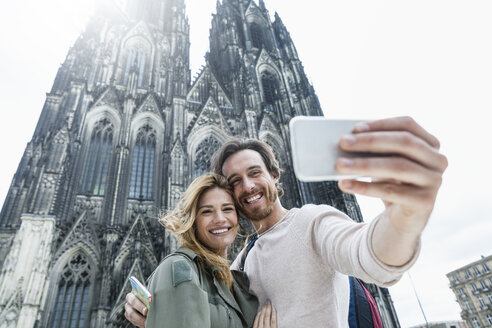 Germany, Cologne, portrait of young couple taking a selfie in front of Cologne Cathedral - FMKF001828