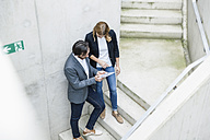 Two business people standing on stairs looking at digital tablet - FMKF001833