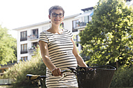 Portrait of smiling pregnant woman with bicycle - SGF001836