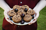 Man holding plate with vegan chocolate muffins with cherries - EVGF002102