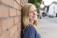 Portrait of happy blond woman leaning on brick wall - SHKF000331