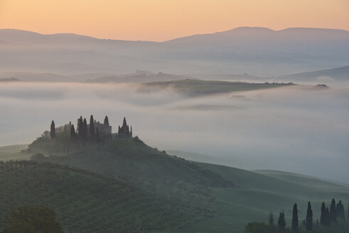 Italy, Tuscany, San Quirico d'Orcia, view to rolling landscape at sunrise in the fog - LOMF000053