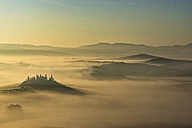 Italy, Tuscany, San Quirico d'Orcia, view to rolling landscape at sunrise in the fog - LOMF000038