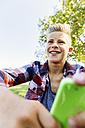 Happy teenage boy with smartphone outdoors - AIF000070