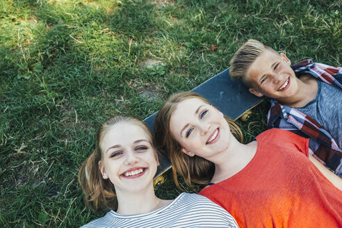 Three happy teenage friends lying on skateboard in meadow - AIF000074