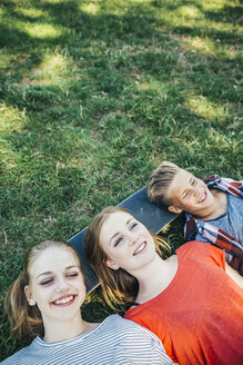 Three happy teenage friends lying on skateboard in meadow - AIF000076