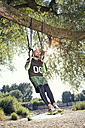 Man doing CrossFit exercise on rings hanging on tree trunk - MAEF010854