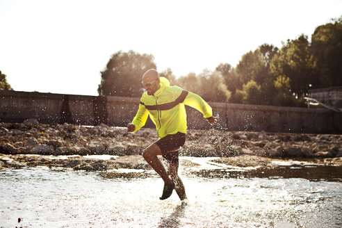 Man in sports wear running in water - MAEF010907