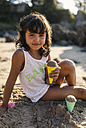 Spain, Llanes, portrait of little girl playing with sand on the beach - MGOF000427