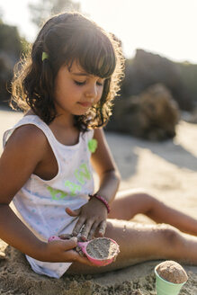 Spain, Llanes, little girl playing with sand on the beach - MGOF000429
