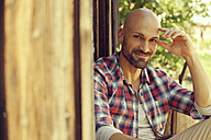 Portrait of smiling man wearing checked shirt sitting in front of wooden hut - MAEF010923