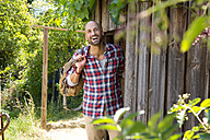 Smiling man standing at entrance door of wooden hut - MAEF010931