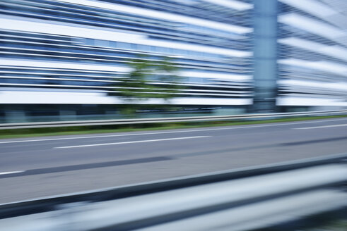 Germany, blurred office building with urban motorway in the foreground - GUFF000134
