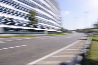 Germany, blurred office building with empty street in the foreground - GUFF000136