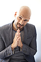 Portrait of bald man in grey suit asking for forgiveness - MAEF010949